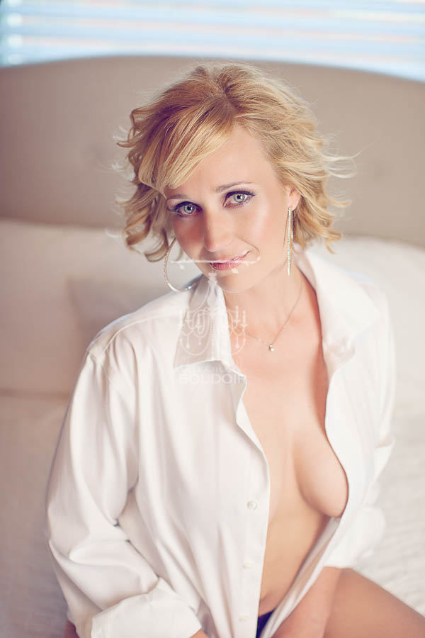 woman in mens shirt blowing hair boudoir portrait
